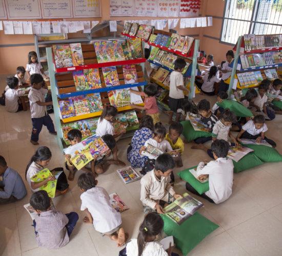 Kinder, die in einer Bibliothek Bücher anschauen