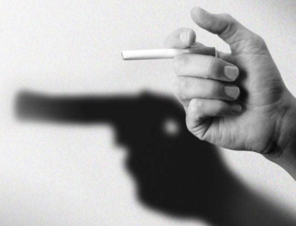 Hand mit Zigarette. Der Schatten sieht wie ein Revolver aus