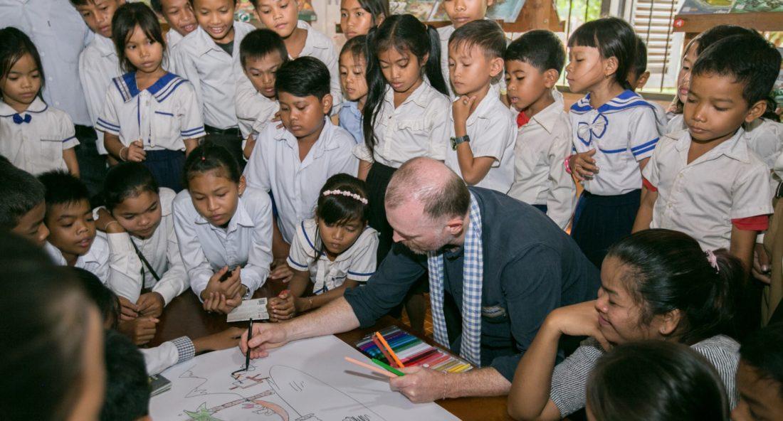 Eine Gruppe von Kindern schaut einem Illustrator bei der Arbeit zu