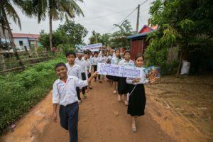 Room to Read: Eine Gruppe von Kindern in Kambodscha, mit Büchern und Plakaten