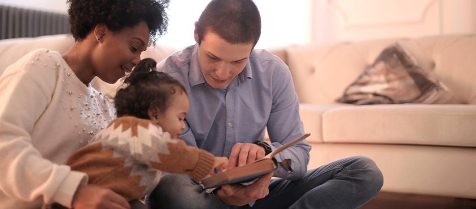 Vorlesern: Familie schaut ein Buch an